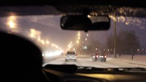 City traffic in winter at night. City traffic in winter through the window stock video footage