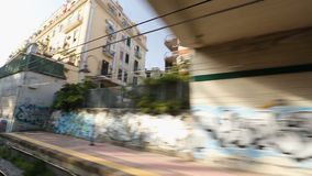 City train going through passageway with graffiti walls and buildings in Naples. Stock footage stock video footage