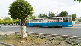 City tram on the street of Temirtau, Kazakhstan. The old tram on the road is on a straight section of the road along. Republic Street Stock Photography