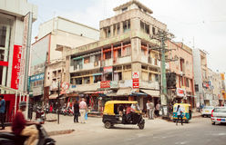 City transport with traditional indian auto-rickshaw on street with shops Royalty Free Stock Photos