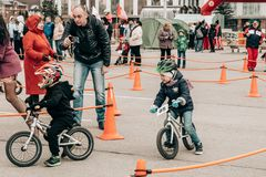 City Tula. Russia - April 06, 2019: amateur competition of children to balance bicycle on Lenin Square. Dad shoots his son on the phone royalty free stock images