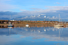 The city of Ushuaia, boats and mountains in the background are reflected in the water Stock Photography