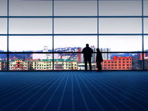 City View. Man and son view the city from large glass window Royalty Free Stock Photo