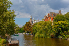 City view of Amsterdam canal, jetty and boat, Holland, Netherlan Royalty Free Stock Image