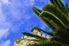 View of Torre del Oro in Seville, Spain. City view with Torre del Oro in Seville Spain and cloudy sky, detail of roof with palm stock photos