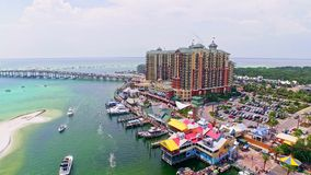 City waterfront harbor by the ocean. Aerial of a shallow marine harbor at vacation resort city front spot with beaches in background. People swimming, boats stock footage