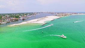 City waterfront by shallow ocean lagoon by the beach. Aerial of a shallow ocean blue water lagoon vacation resort spot with beaches in background. People stock video footage