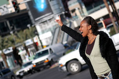 City Woman. Beautiful African American woman stopping Traffic, Hailing a cab Stock Photo