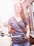 City Woman with Phone and Bicycle Stock Photo