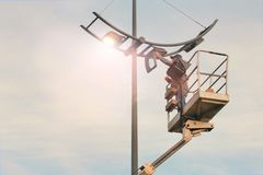 City Worker electrician installs a bulb into a street lamp. Profession that provides comfort, electricity in cities.