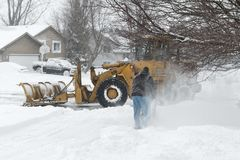 City Worker And Homeowner Clearing Snow Stock Photos