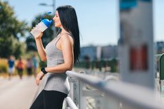 City workout. Beautiful woman with a smartwatch training in an urban setting Royalty Free Stock Photography