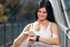 City workout. Beautiful woman with a smartwatch training in an urban setting. City workout. Beautiful young woman with a smartwatch training in an urban setting Royalty Free Stock Photography