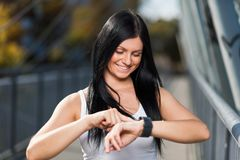 City workout. Beautiful woman with a smartwatch training in an urban setting. City workout. Beautiful young woman with a smartwatch training in an urban setting Stock Images