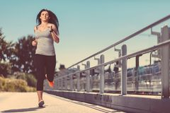 City workout. Beautiful woman running in an urban setting Stock Images