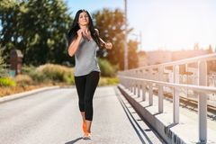 City workout. Beautiful woman running in an urban setting Royalty Free Stock Photo