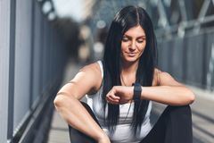 City workout. Beautiful woman with a smartwatch training in an urban setting. City workout. Beautiful young woman with a smartwatch training in an urban setting Stock Image