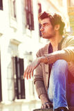 City young handsome man. Urban sitting model. Building windows Royalty Free Stock Image