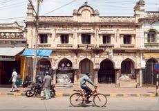 Citylife med cyklisten och motorcykeln på gatan av den indiska staden med byggnader i kolonial stil Royaltyfri Foto