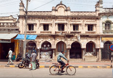 Citylife met fietser en motorfiets op straat van Indische stad met gebouwen in koloniale stijl Royalty-vrije Stock Foto