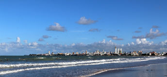 Cityline of Joao Pessoa, ocean and waves and surfers waiting for a big wave royalty free stock photography