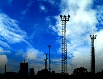 Cityscape. High cell tower silhouettes and blue sky royalty free stock images