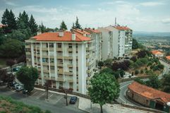 Cityscape with apartment building in the midst of trees. And hilly landscape, in a cloudy day at Covilha. Known as the town of wool and snow, stands at Estrela stock photography