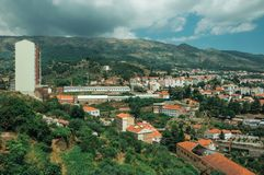 Cityscape with apartment building in the midst of trees. And mountainous background, on cloudy day at Covilha. Known as the town of wool and snow, stands at stock photo