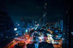 Cityscape av den berömda Maha Nakhon Tower i Bangkok, Thailand Ljusa slingor i gatorna från bilarna Mörk himmel bak fotografering för bildbyråer