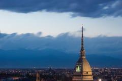 Cityscape av Torino Turin, Italien på skymning med dramatisk himmel över fjällängarna Vågbrytaren Antonelliana står högt på stade Royaltyfria Bilder