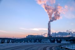 Cityscape, background bridge, smoke of factory pipes pollutes atmosphere. Concept of oil, coal, gas processing, pollution of en stock photography