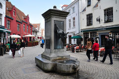 Cityscape of Bruges, Belgium. Cityscape of Bruges with tourists, local cafes & bistro, and bronze sculpture of horse head water fountain, Belgium Stock Images