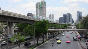 Cityscape and BTS or Skytrain running to stop at Mo Chit railway station with people walking and traffic at Chatuchak Market. BANGKOK, THAILAND - APRIL 15 stock video