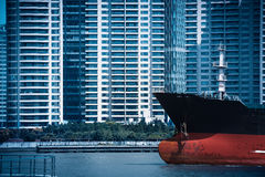 cityscape of cargo ship with modern buildings Stock Photography