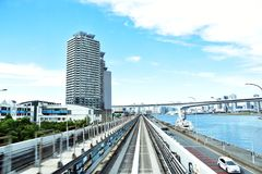 Picture inside a commuter train in Tokyo aproaching the end of Odaiba`s Rainbow bridge. Cityscape from commuter train view in tokyo Royalty Free Stock Photo