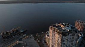 cityscape Complesso residenziale sulla sponda del fiume Metraggio aereo da un elicottero a tempo di tramonto stock footage