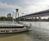 Ship moored under the UFO Bridge in Bratislava, Slovakia. Cityscape with Danube river and passenger ship moored under the SNP New bridge or UFO Bridge in Royalty Free Stock Photo