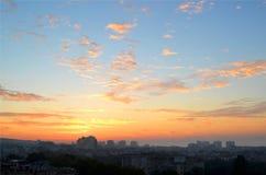 Cityscape in de vroege ochtend: roze en oranje wolken op een blauwe hemel bij dageraad vlak vóór zonsopgang over de slaapstad royalty-vrije stock afbeeldingen