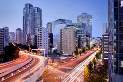 Cityscape at Dusk in Shinjuku District, Tokyo, Japan. Tokyo skyline at dusk in Shinjuku district with fast traffic flowing on the highway Royalty Free Stock Photo