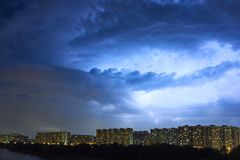 Cityscape at dusk with thunderstorm over apartments buildings Royalty Free Stock Images