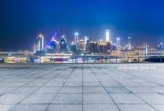 Cityscape en horizon van het chongqing van lege baksteenvloer bij nacht stock afbeelding