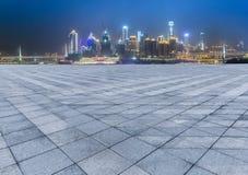 Cityscape en horizon van het chongqing van lege baksteenvloer bij nacht stock afbeeldingen