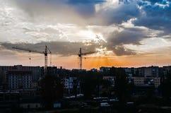 Cityscape för konstruktionskran på solnedgånghimmelbakgrund Arkivbilder