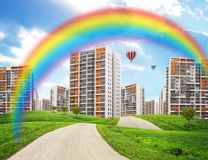 Cityscape on green field with rainbow Royalty Free Stock Photography