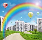 Cityscape on green field with rainbow and trees Royalty Free Stock Photos