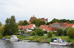 Cityscape of Havelberg (Germany, Saxony-Anhalt) with Havel River. And boat and cathedral high above the town Stock Photo