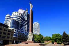 Cityscape. High towers, skyscrapers and and the monument of Glory in Dnipro city against the blue sky, Dnepropetrovsk, Dnepr. Cityscape. High towers, skyscrapers stock photos