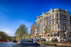 Cityscape with historic buildings and boats on canal in Amsterdam, Netherlands. AMSTERDAM, NETHERLANDS - MAY 6, 2016: Cityscape with historic buildings and boats royalty free stock image