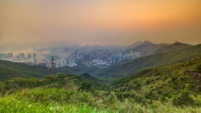 Cityscape of Hong Kong as viewed atop Kowloon Peak with sunset timelapse with Hong kong and Kowloon below. Foggy weather with green grass on hills. 4K stock video