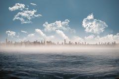 Cityscape on horizon over ocean Stock Photo